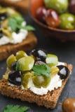 Rye bread toast canape with kalamata, black and green olives, feta chees. Rye bread toast canape with kalamata black and green olives, feta cheese and parsley stock photos