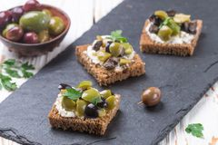 Rye bread toast canape with kalamata, black and green olives, feta chees. Rye bread toast canape with kalamata black and green olives, feta cheese and parsley royalty free stock photography