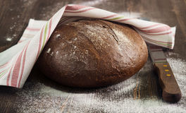Rye bread under towel on wooden table Stock Image