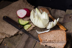 Rye bread, vegetables and knife on an old table. Rural style, old gray boards, dark background. The big white bulb cut as a flower, segments of a cucumber and Royalty Free Stock Photo
