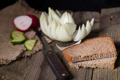 Rye bread, vegetables and knife on an old table Stock Images