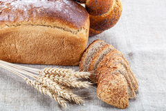 Rye bread, wheat loaf with poppy seeds and ears on sacking Stock Photos