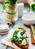 Rye bread with wild garlic, sour cream and quail eggs Royalty Free Stock Photos