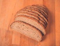 Rye-Brot auf einem Holztisch Beschneidungspfad eingeschlossen Frisches wohlriechendes knusperiges geschnittenes Brot Stockbild
