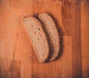 Rye-Brot auf einem Holztisch Beschneidungspfad eingeschlossen Frisches wohlriechendes knusperiges geschnittenes Brot Lizenzfreie Stockfotos