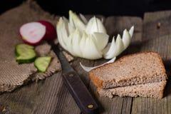 Rye-Brot, -gemüse und -messer auf einer alten Tabelle Stockbilder