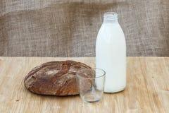 Rye-Brot mit Flasche Milch auf Holztisch Stockbilder