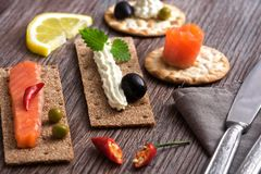 Rye crackers and crackers with cheese and red fish on a wooden table. Rye crackers and crackers with cheese and red fish on a wooden table Royalty Free Stock Photo