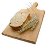 Rye ears (spikes) and loafs of bread on wooden board Stock Photos