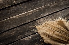 Malt, hop and rye ears. Rye ears wrapped in burlap cloth on aged wooden table background with copy space royalty free stock image