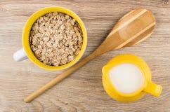 Rye forma escamas en la cuchara del taza, de bambú y el jarro de leche Fotos de archivo libres de regalías