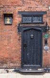 RYE, Großbritannien/CIRCA im Mai 2014 - eine alte Backsteinmauer mit der schwarzen Holztür gesehen in Rye, Kent, Großbritannien Lizenzfreie Stockfotos