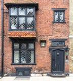 RYE, Großbritannien/CIRCA im Mai 2014 - eine alte Backsteinmauer mit der schwarzen Holztür gesehen in Rye, Kent, Großbritannien Lizenzfreie Stockbilder
