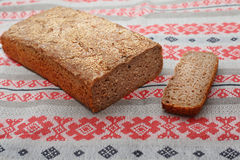 Rye home-made bread with cutted slice of bread on the folk-style tablecloth Stock Photos