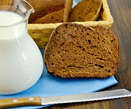 Rye homemade bread with milk and a knife on a board Stock Photo