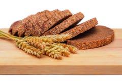 Rye malt bread and wheat ears. Slices of rye malt bread and wheat ears on the chopping board Stock Photo