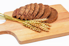 Rye malt bread and wheat ears. Slices of rye malt bread and wheat ears on the chopping board stock photography