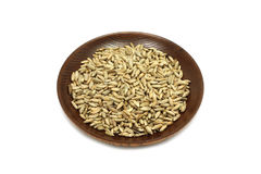 Rye malt grains in a wooden plate. On a white background stock photos