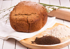Rye meal, malt and bread. On white wooden table stock photos