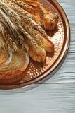 Rye-Ohren backten Gebäckmessingbehälter auf hölzernem Hintergrund Lizenzfreie Stockbilder