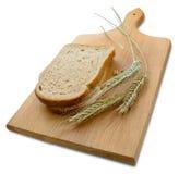 Rye-Ohren (Spitzen) und Laibe des Brotes auf hölzernem Vorstand Stockfotos