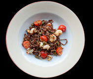 Rye pasta with capers and prawns. Isolated on black background Royalty Free Stock Photography