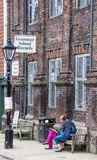 RYE, Reino Unido/1r de junio de 2014 - dos mujeres desconocidas se están sentando en un banco delante de la tienda de los expedie Imagen de archivo