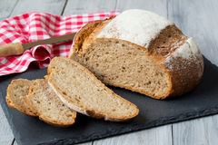 Rye round bread on stone cutting board with napkin and knife on wooden background Stock Photos