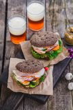 Rye sandwiches with ham and letucce on wood table with two glasses of beer Royalty Free Stock Photos