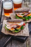 Rye sandwiches with ham and letucce on wood table with two glasses of beer Stock Images