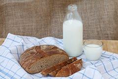 Rye schnitt Brot mit Flasche Milch auf Holztisch Stockbild