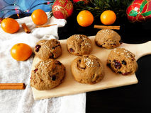 Rye scones surrounded by Christmas decorations. Rye scones with dried cranberries on a wooden board surrounded by Christmas decorations royalty free stock images