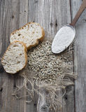 Rye seeds with slices of bread and flour. On wood background Stock Photos
