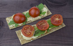 Rye snack with hummus and tomatoes. Rye snack with hummus, tomatoes and arugula on a dark wooden background Stock Images