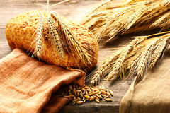 Rye spikelets and bread still life on wooden background Stock Photo