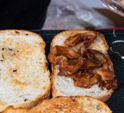 Rye toast with bacon on griddle royalty free stock image