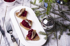 Rye toasts with herring and beets. On plate on wooden background stock photos