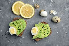 Rye toasts with sliced avocado and quail eggs. On table, top view Stock Photos