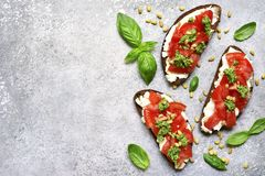 Rye toasts with soft cheese, tomatoes, pine nuts and pesto sauce. On a light grey slate, stone or concrete background. Top view with copy space stock photo