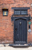 RYE,UK / CIRCA MAY 2014 - An old brick wall with black wooden door seen in Rye, Kent, UK Royalty Free Stock Photos