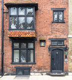 RYE,UK / CIRCA MAY 2014 - An old brick wall with black wooden door seen in Rye, Kent, UK Royalty Free Stock Images