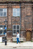 RYE,UK / 1st of JUNE 2014 - An unknown man walking in front of an old brick house Royalty Free Stock Images