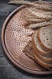 Rye wheat ears sliced loaf of bread vintage brass tray food and Royalty Free Stock Images