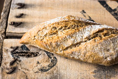Rye whole wheat bread loaf on vintage wood box, top view, close up Royalty Free Stock Images