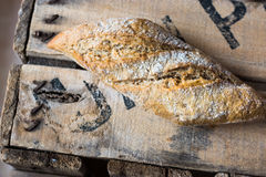 Rye whole wheat bread roll with golden crust dusted with flour on wood box, top view Royalty Free Stock Photography