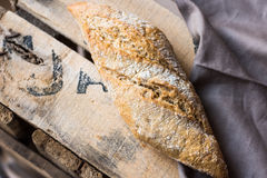Rye whole wheat bread roll with golden crust dusted with flour on wood vintage box, grey linen napkin, top view Royalty Free Stock Photo