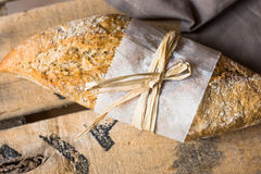 Rye whole wheat bread roll with golden crust wrapped in parchment paper on wood vintage box, grey linen napkin Stock Images