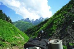 Ryggsäck i bergen med härligt sommarlandskap på begreppet av bakgrund för livsstilsportklättring Arkivbild