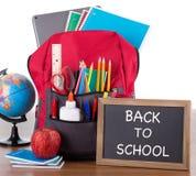 Ryggsäck med skolatillförsel och den svart tavlan royaltyfri foto