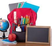 Ryggsäck med skolatillförsel och en tom svart tavla royaltyfri bild